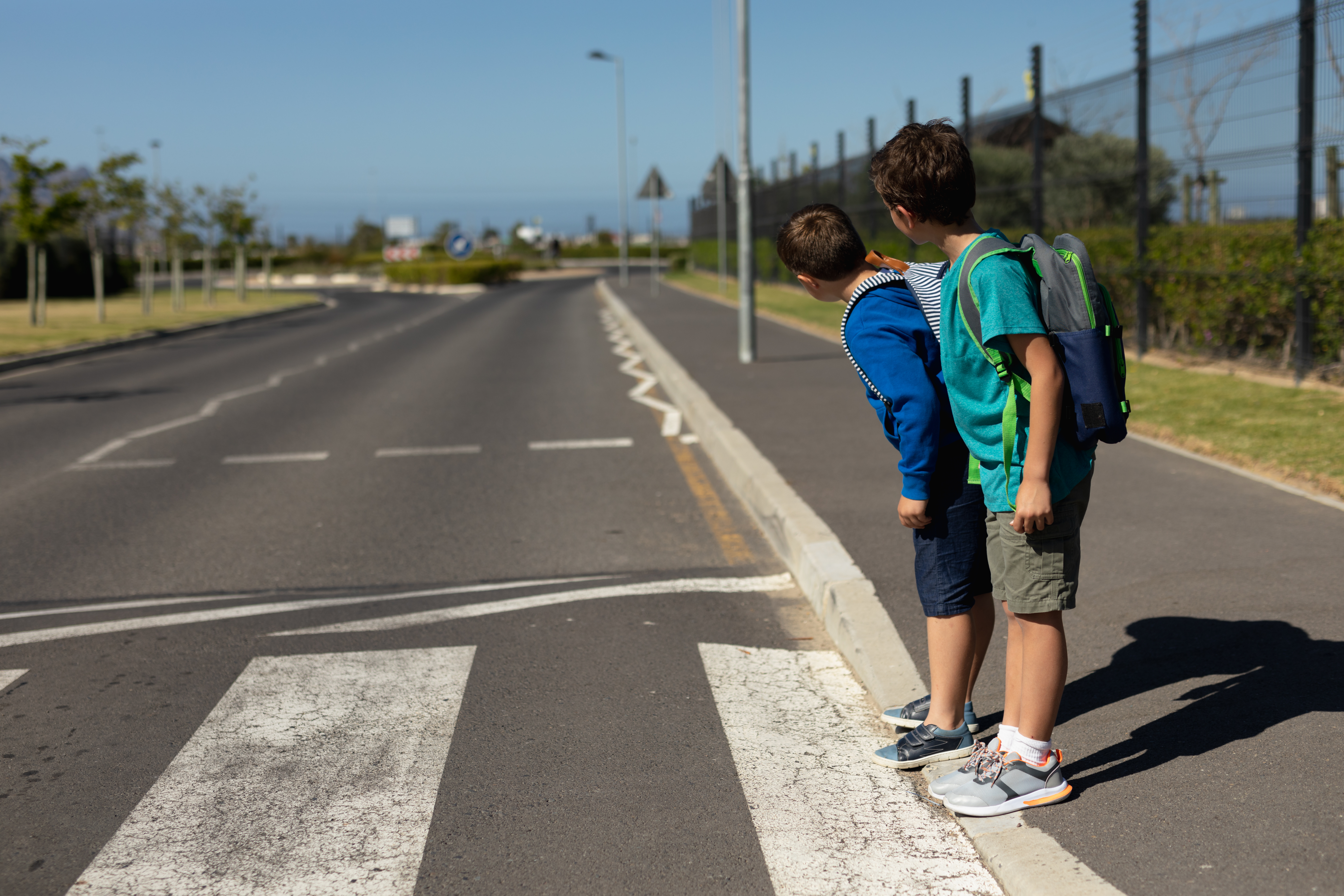 two-schoolboys-looking-for-traffic-while-waiting-2ANF2WV.jpg (Two schoolboys...
